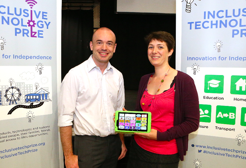 Kate and Joe holding a tablet in front of an 'inclusive technology Prize' sign
